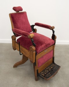 Barber chair from 1898. Crushed red velvet with wooden attachments
