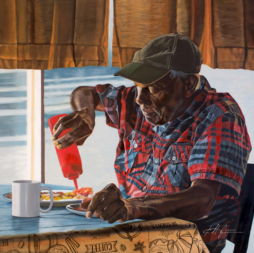 Older black man in plaid shirt and cap squeezing ketchup on to food in a diner