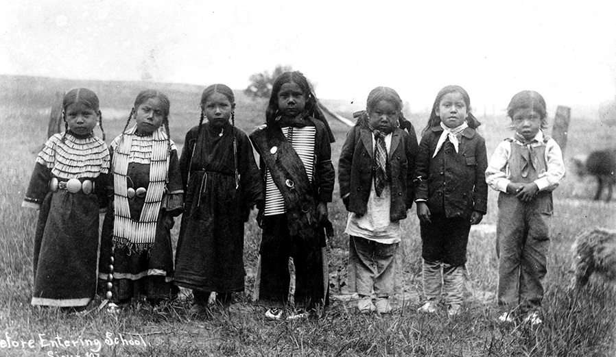 photo from 1897 of 7 Native American children lined up. They are wearing traditional clothing and all look to be about 5 to 6 years old.