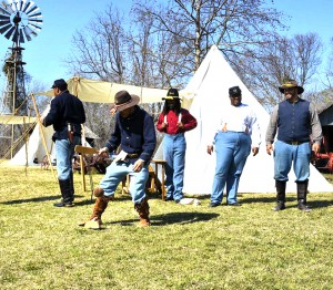 Members of the Texas Buffalo Soldiers Program recreate a game of frontier baseball called Trap. The men are dressed in period 1870s military uniforms and are playing in front of tent.