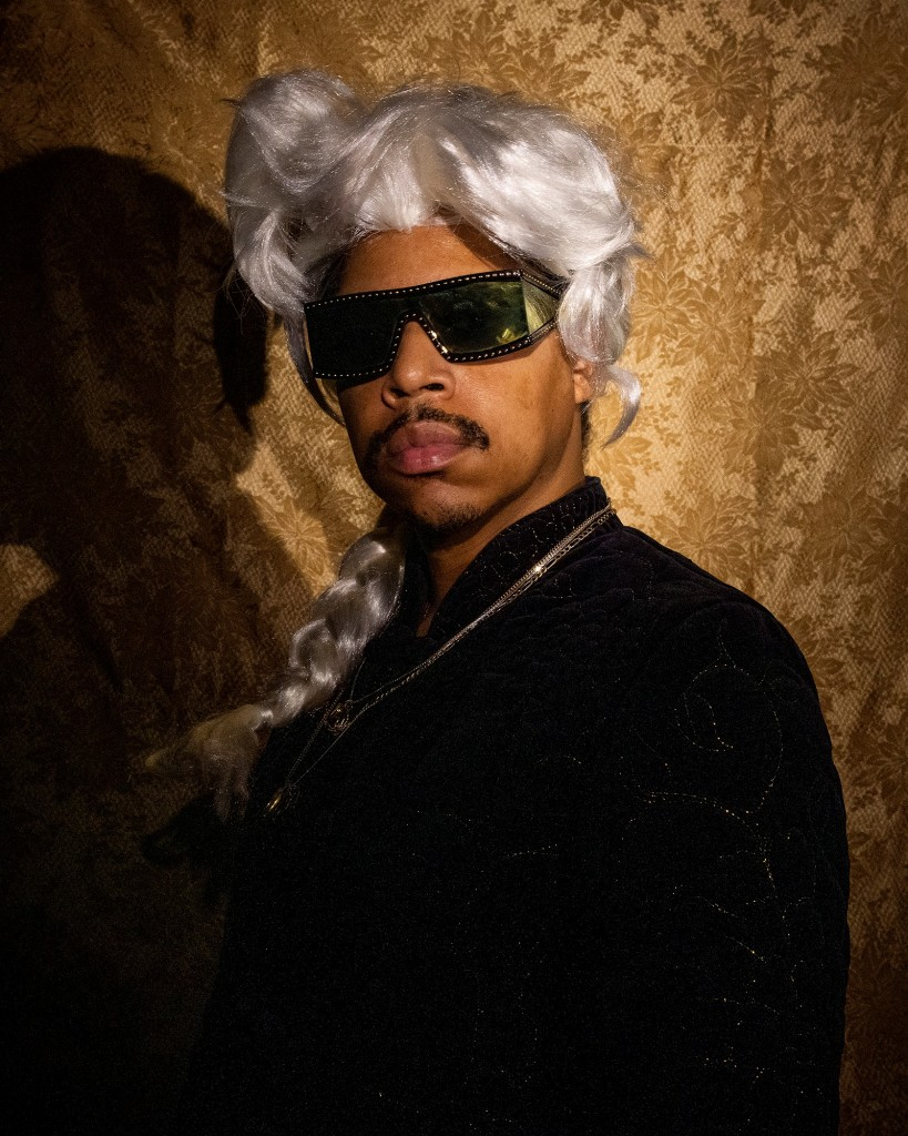 photo portrait of artist wearing white wig and sunglasses