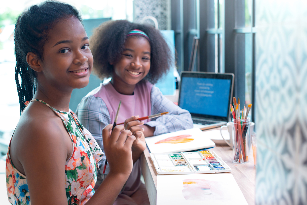 two black teenage girls painting at a desk. Both girls are looking at the cam. The girl closest to the camera is wearing a multi-colored sundress and has brains. The girl in the background has natural hair and is wearing a pink vest and a blue headband. era