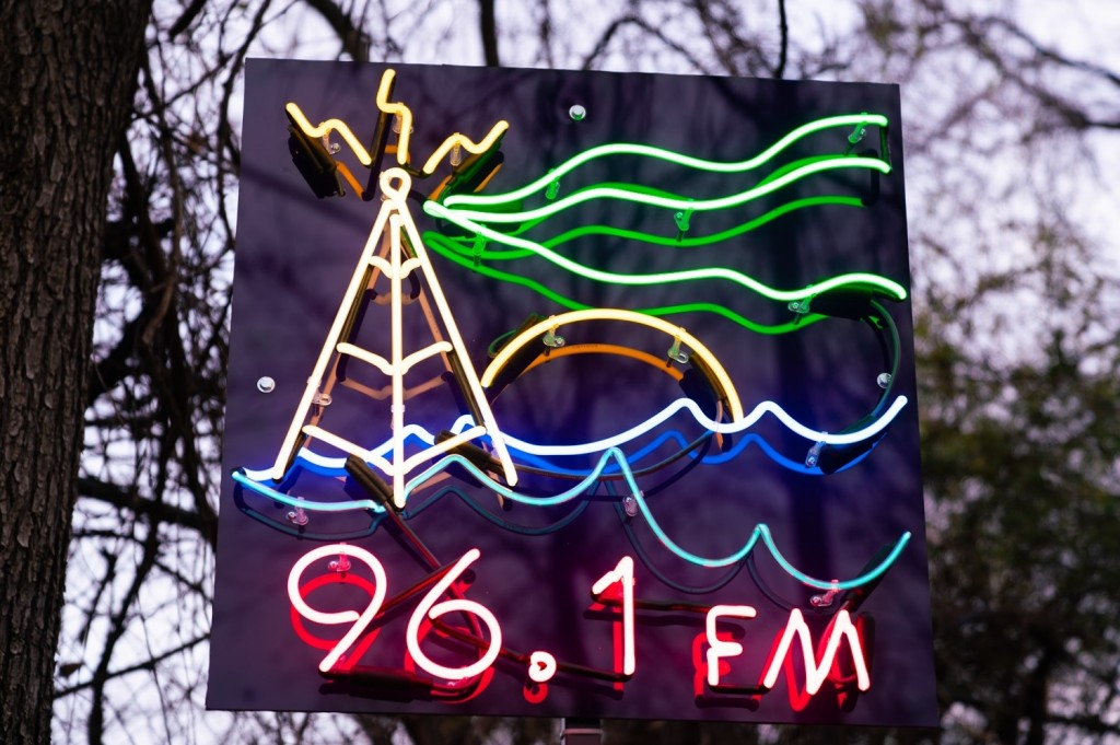 neon sign of radio tower and waves and 96.1 FM on it and posted by trees