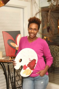 Visual Artist poses in front of painting holding a palette.