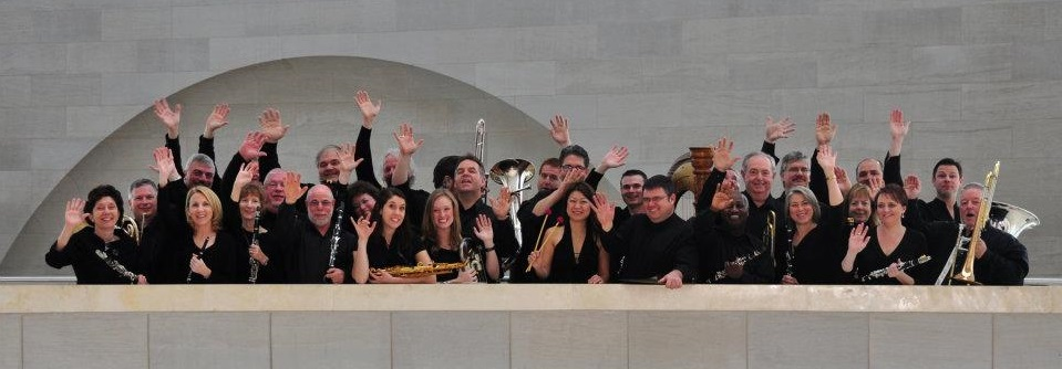 The Dallas Winds band gathered on a balcony. The group has their instruments and are waving happily.