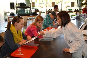 three young girls are gathered at table. Woman wearing lab coat hands one of the girls a clipboard.