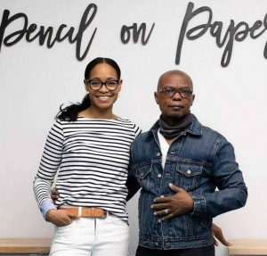 Black women and man posing in front of lettering that reads 'Pencil on Paper' Woman is 30ish with glasses wearing a black and white striped top and white jeans. Man is 50ish with glasses where a t-shirt and jean jacket.