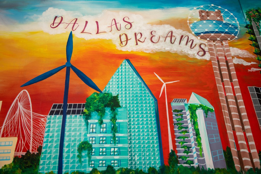 """A part of the painted mural with the words """"Dallas Dreams"""" over wind turbines, green roofs and green canopy spaces."""