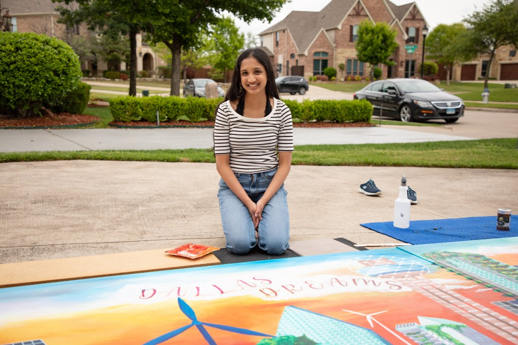 A girl sits in front of a brightly colored mural.