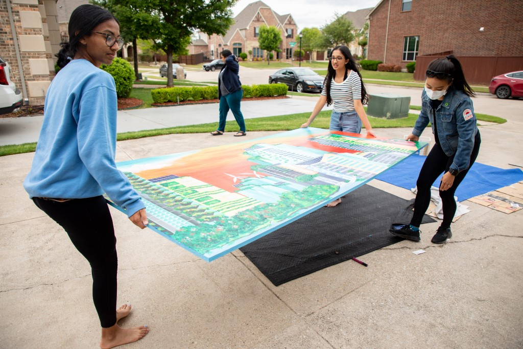 Three people carry a piece of the mural.