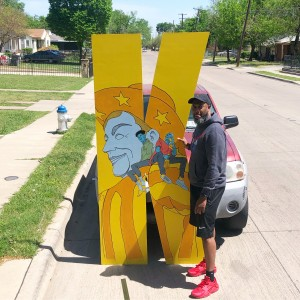Black man holds up the 8-foot tall letter K. The letter is yellow and has a painting of Big Tex on it.