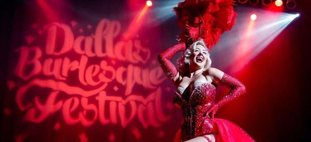 """Blonde woman in red sequined costume on stage. She's smiling and holding a red feather fan above her head. Behind her projected on screen are the words """"Dallas Burlesque Festival."""""""