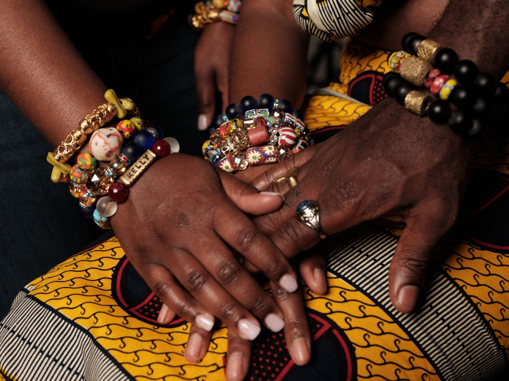 Close up of three Black hands. The hands are wearing a variety of colorful African bracelets and rings