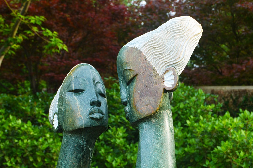 Two stone sculptures in a garden setting. The sculptures are busts of two women with long necks.