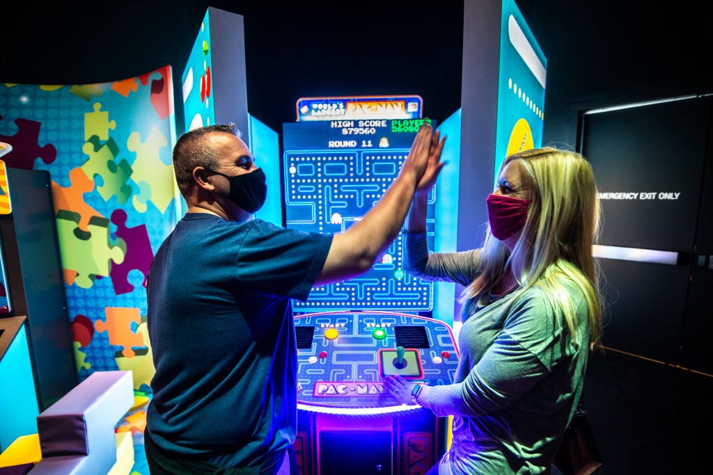 Man in blue shirt hi-fiving woman in green shirt. They are standing in front of a Pac Man machine.