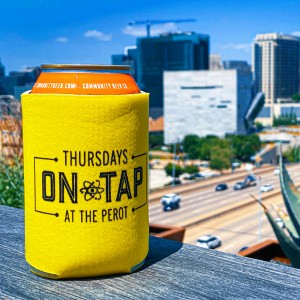 """Single beer in yellow beer cozy with the logo """"Thursdays on Tap at the Perot."""" Beer is sitting on a railing in foreground with view of Perot Museum in the background."""