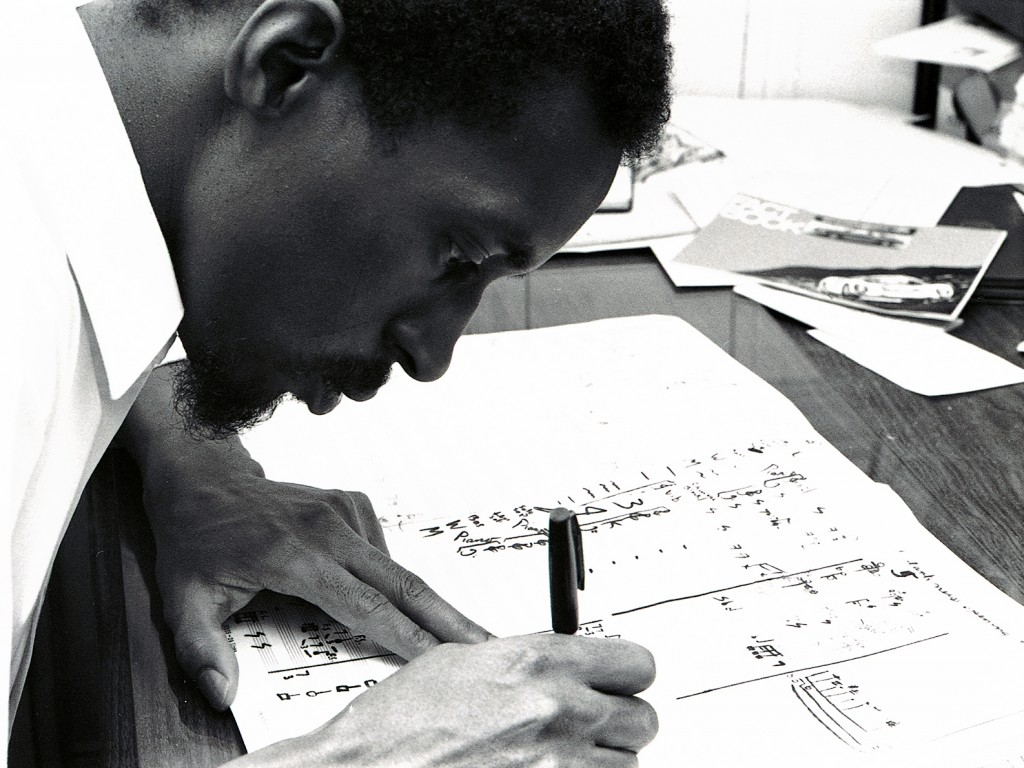 Close profile up black and white photo of a Black man with a goatee composing music