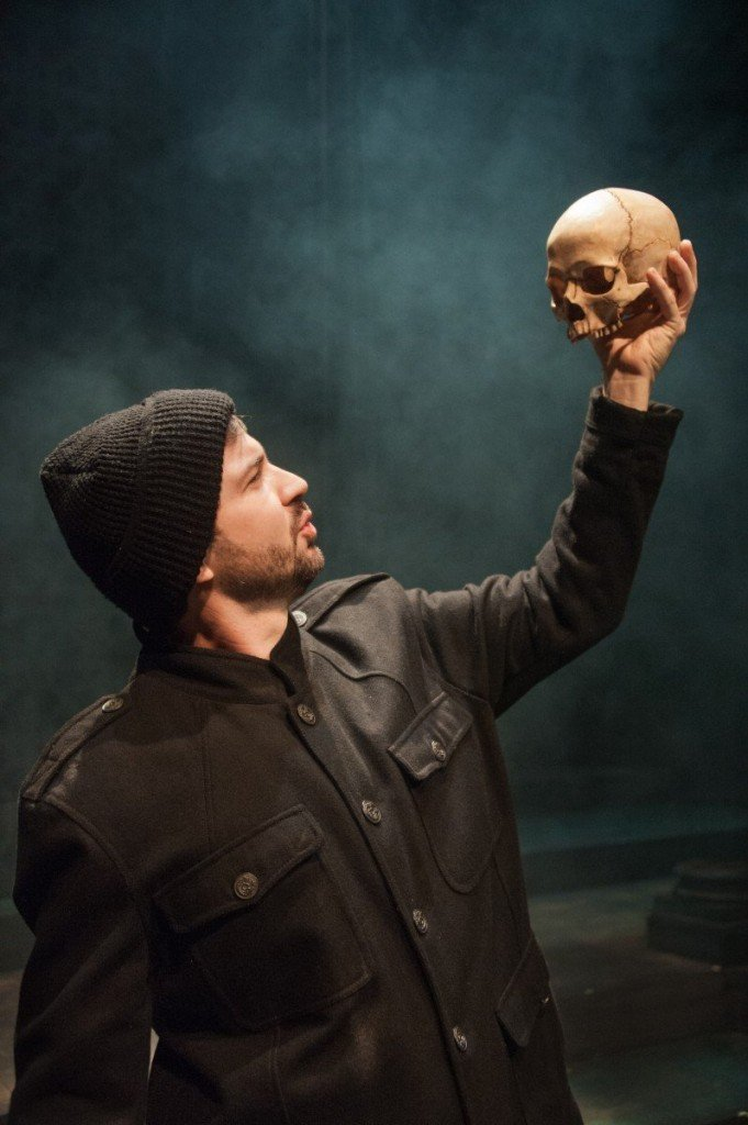 Man wearing knit cap and brown jacket holding up skull