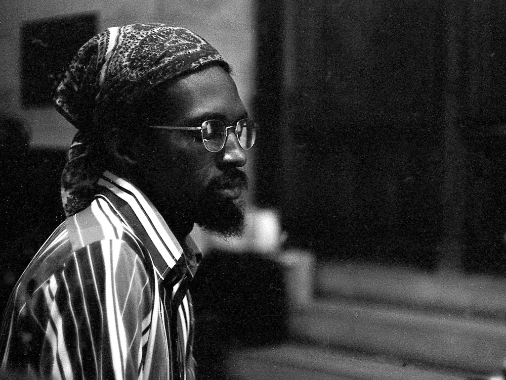 Black and white photo of black man. He's wearing a scarf on his head and a striped shirt and glasses
