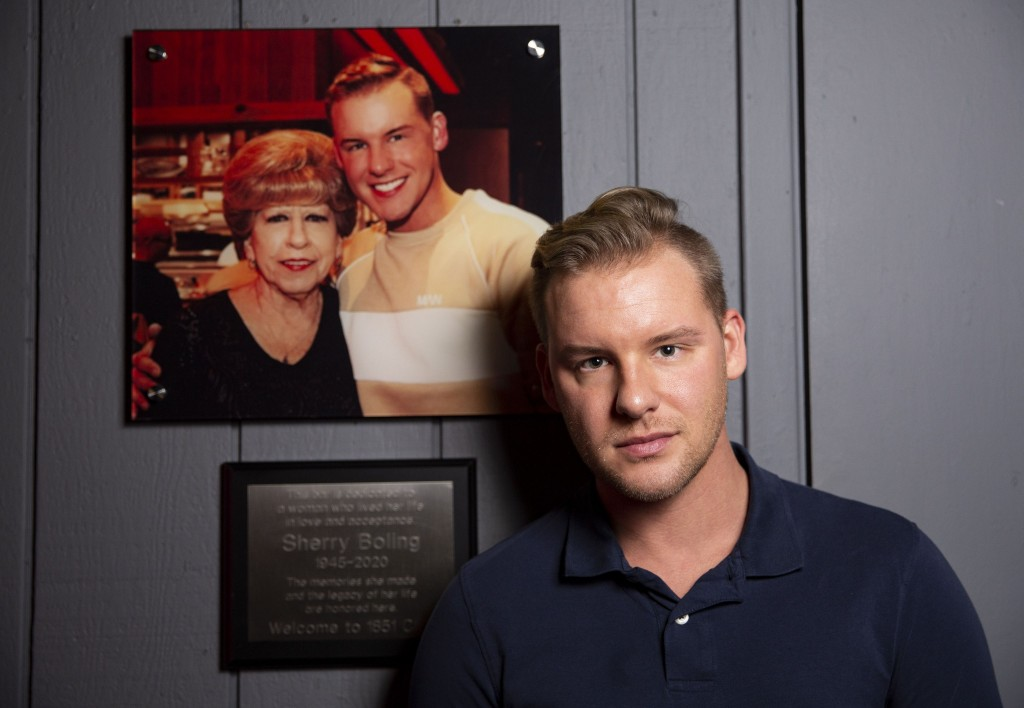 1851 Club owner Dalton Haynes poses for photo next to the plaque honoring his grandmother on Friday, July 2, 2021, at the bar in Arlington. (Juan Figueroa/The Dallas Morning News)